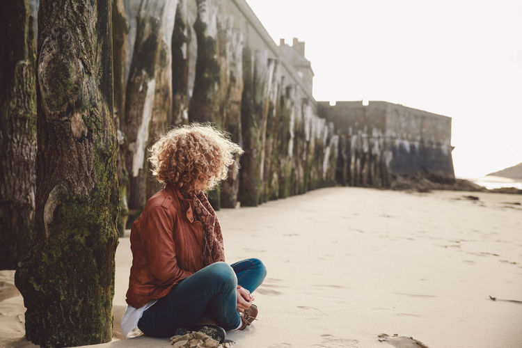Woman sitting at beach against castle