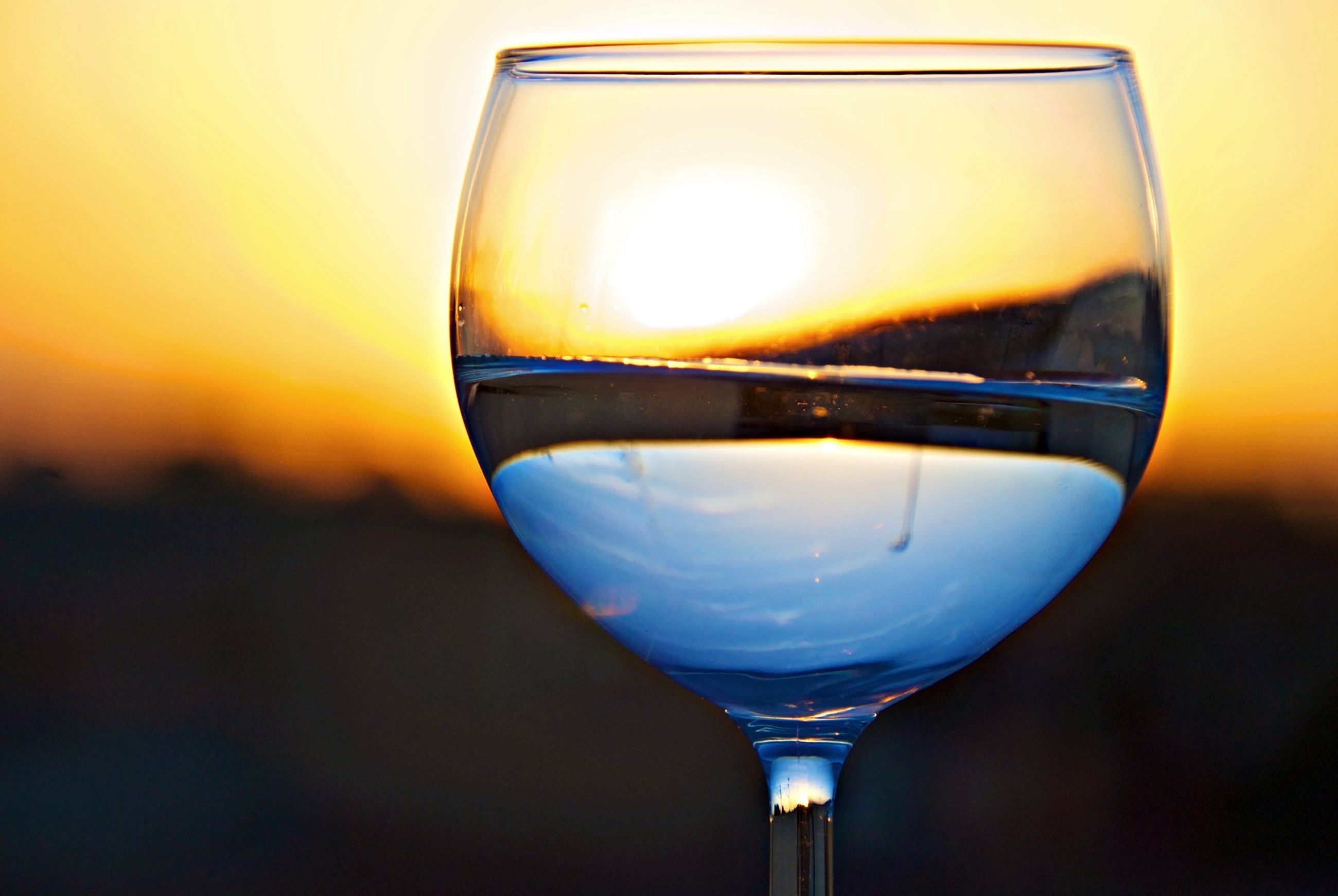 close-up, sunset, transparent, glass - material, refreshment, drink, focus on foreground, drinking glass, food and drink, freshness, alcohol, wineglass, orange color, wine, reflection, sky, indoors, no people, single object, copy space