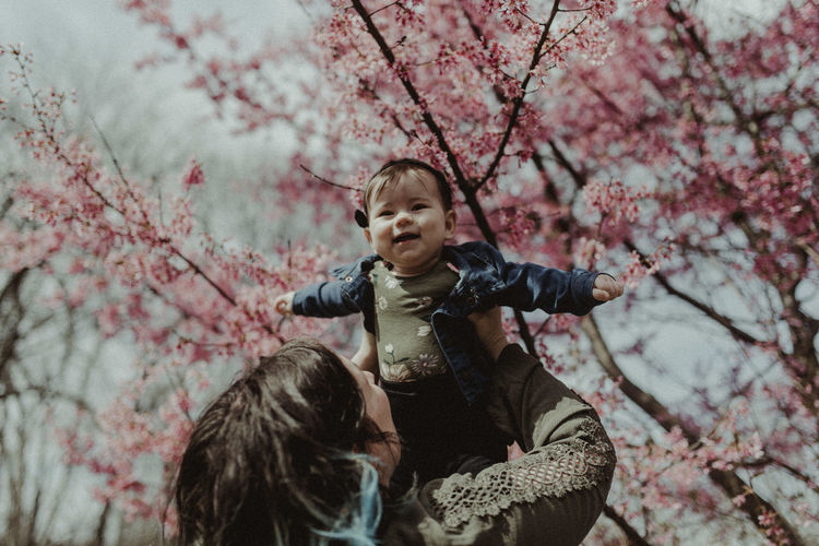 Mother lifting cute daughter against tree