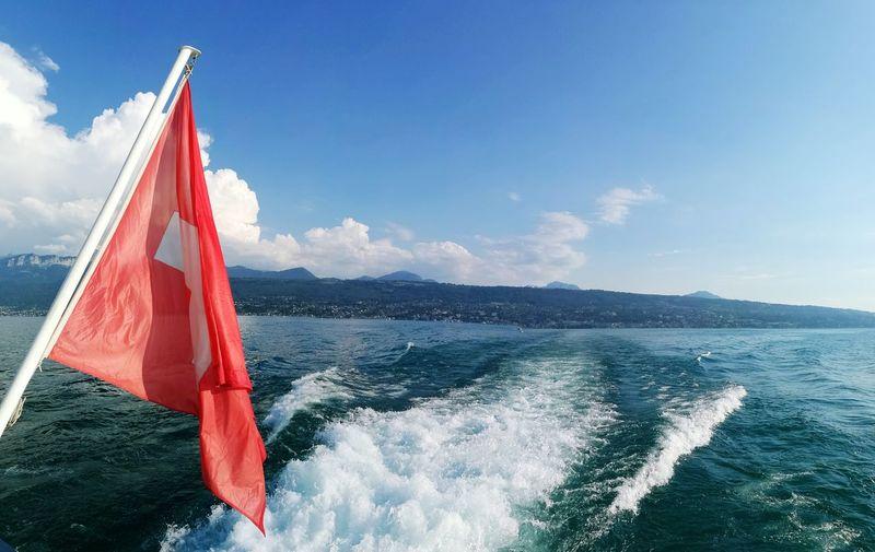 Flag over sea against sky
