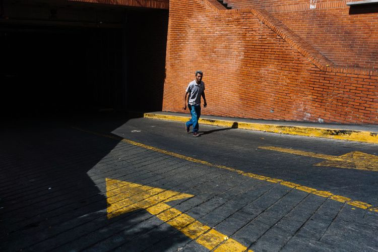 Full length of man walking on road in city