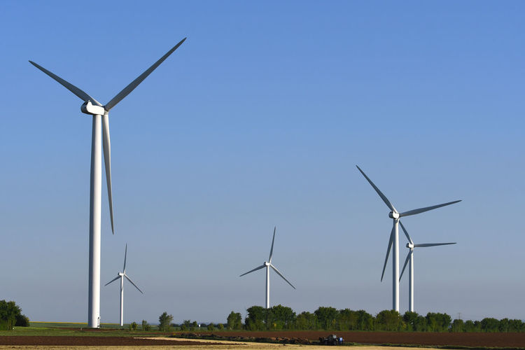 Low angle view of windmills on field against sky
