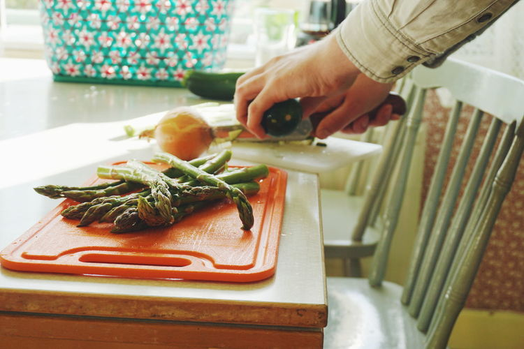 Close-up of person chopping vegetables on cutting board