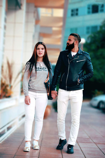 Full length of couple walking on footpath in city