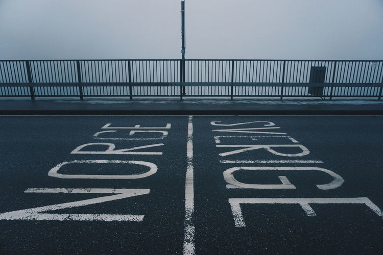Road marking on bridge by railing during foggy weather