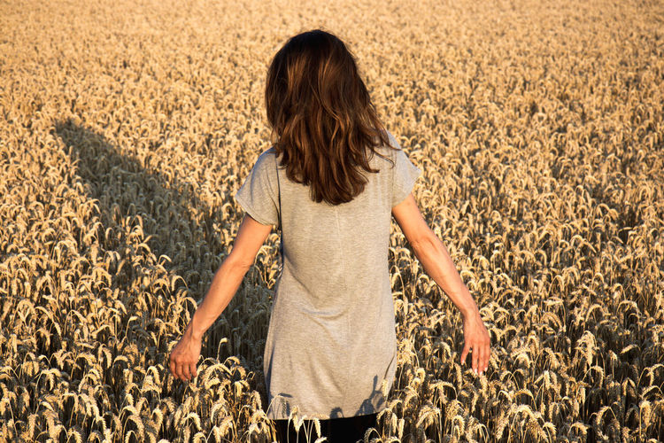 Rear view of woman standing in farm