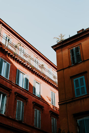 Building Exterior Low Angle View Window Architecture Built Structure Sky Building Clear Sky No People Nature Residential District Outdoors Glass - Material City Copy Space Sunlight In A Row Blue House Apartment Italy Light And Shadow Orange Color Backgrounds Copy Space