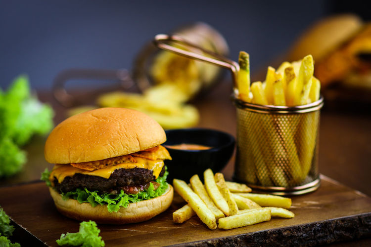 Close-Up Of Burger With French Fries Served On Wooden Table
