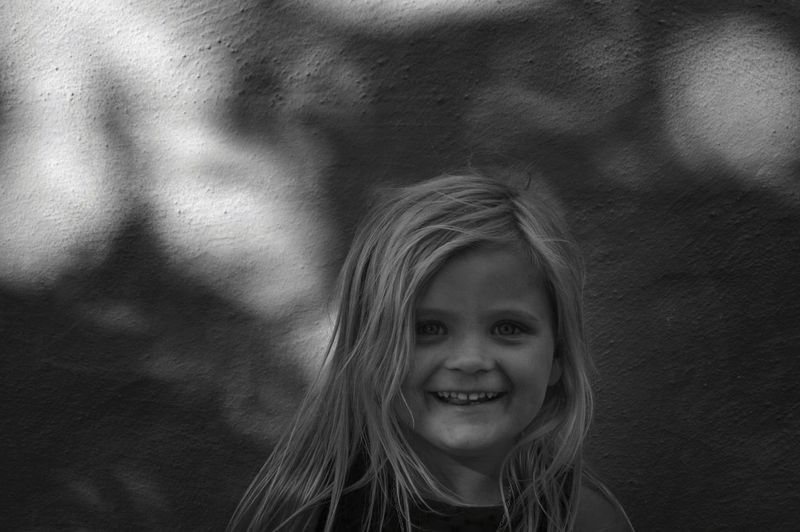 Portrait of smiling girl against wall