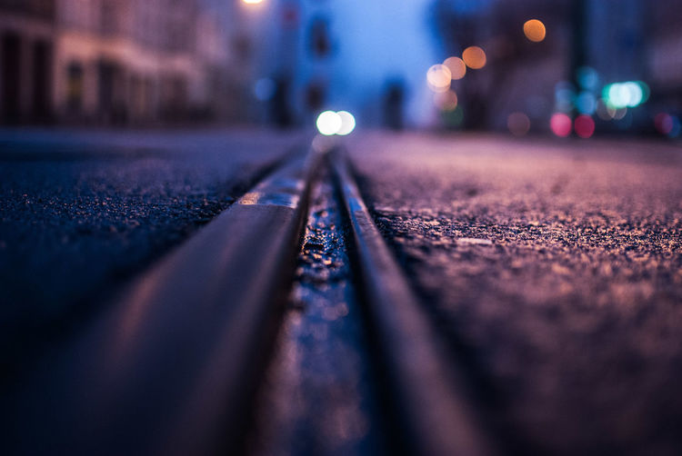 Close-up of railroad track on street in city at night