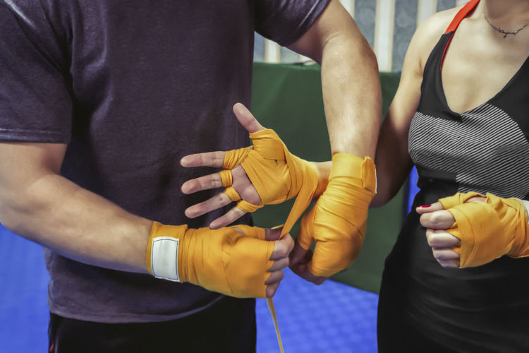 The girl's coach bandages her hands under the boxing gloves. Healthy lifestyle, diet, sports. Close-up Day Human Body Part Human Hand Indoors  Lifestyles Men Midsection Real People Standing Togetherness Yellow