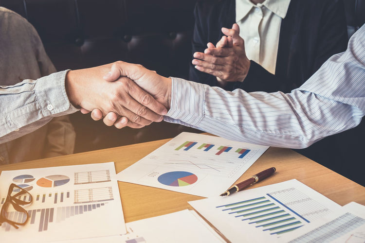 Close-Up Of Business Shaking Hands While Working In Office