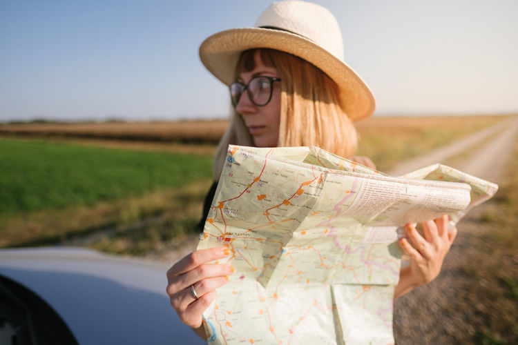 Adult Casual Clothing Clothing Glasses Guidance Hat Holding Journey Leisure Activity Lifestyles Map Mode Of Transportation Nature One Person Outdoors Reading Road Trip Transportation Travel Women Young Adult
