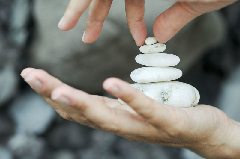 Cropped Hand Stacking Pebbles