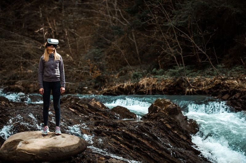 Woman wearing virtual reality simulator while standing against trees