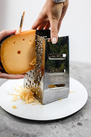 Close-up of person grating cheese