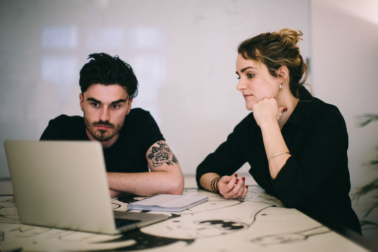 Business people looking at laptop on desk in creative office