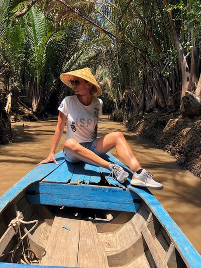Woman sitting on rowboat in river at forest