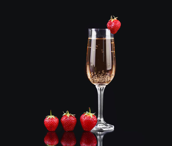 Strawberries in glass against black background