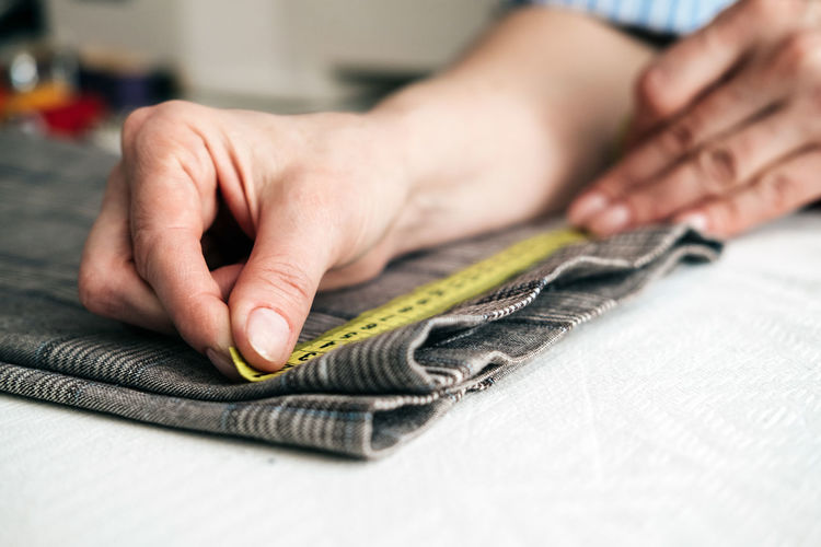 Cropped hands of man measuring fabric on table