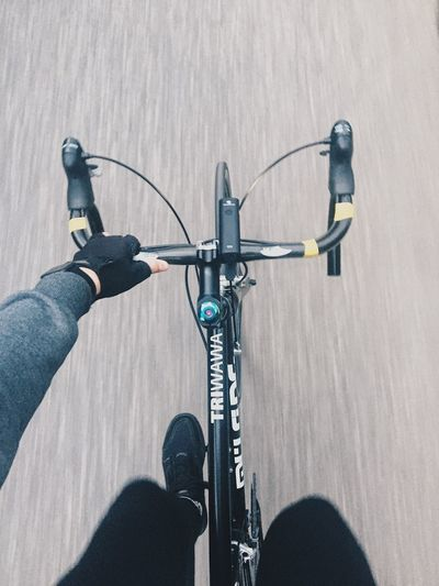 Low section of person riding bicycle on road