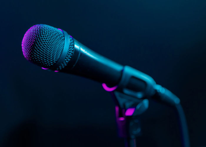 Microphone on black background with colorful pink and turquoise light. Music, concert concept. Microphone Input Device Music Arts Culture And Entertainment Communication Indoors  Technology Studio Shot Close-up No People Audio Equipment Performance Microphone Stand Metal Equipment Musical Instrument Singing Single Object Night Nightlife Speech Stage Silver Colored