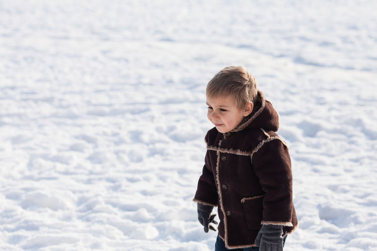 Boy with jacket on snow during winter
