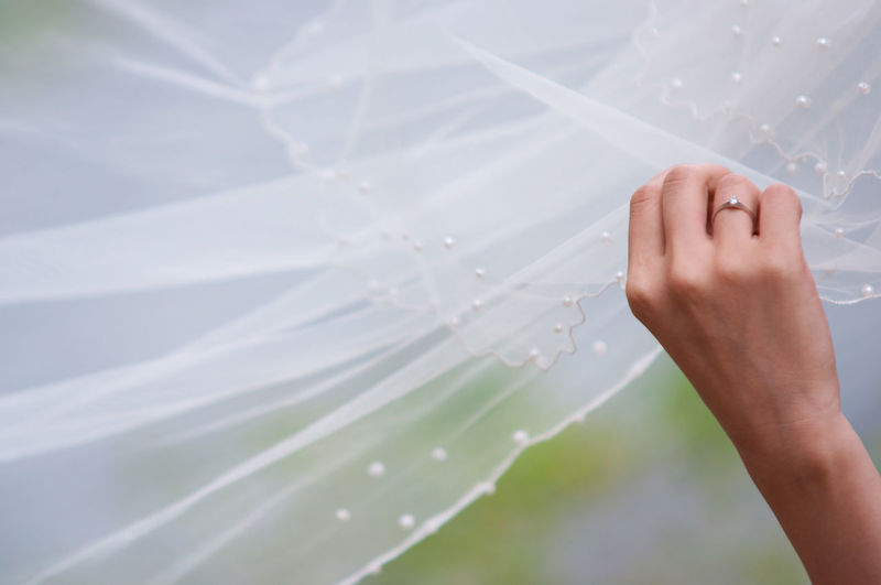 Close-Up Of Hand Holding White Dress