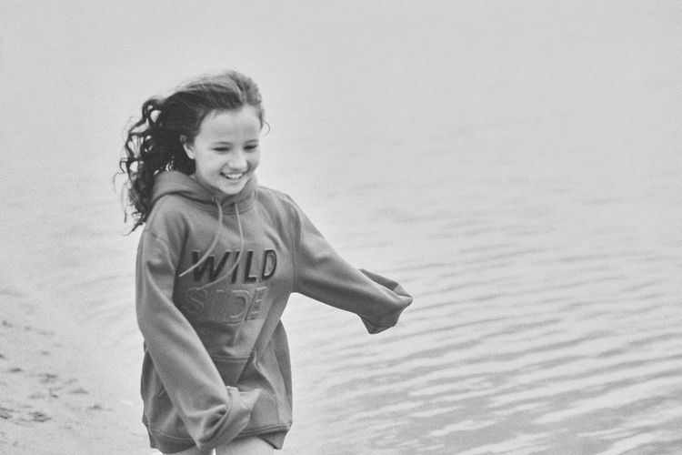 Black and white photo of a girl running along the seashore. happy little girl on summer vacation