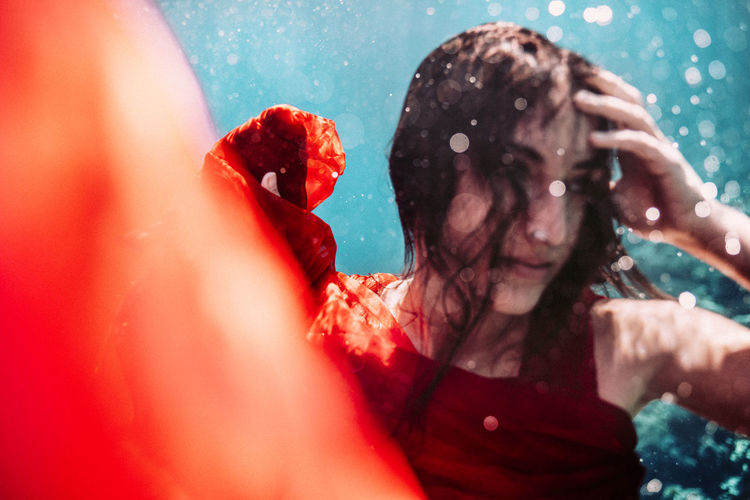 Portrait of woman with red rose in water