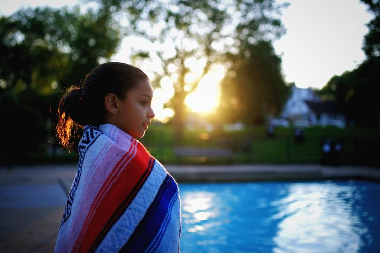Girl Standing By Swimming Pool With Wrapped Towel