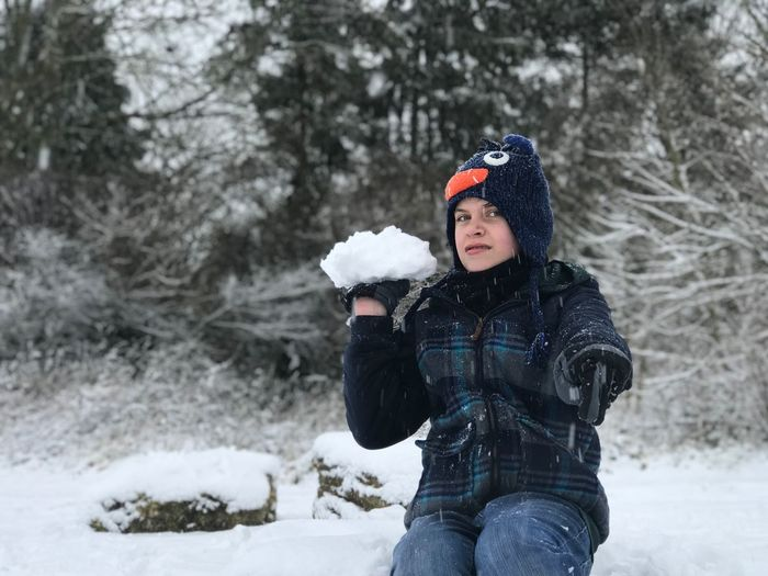 Portrait Of Teenage Boy Throwing Snowball On Field