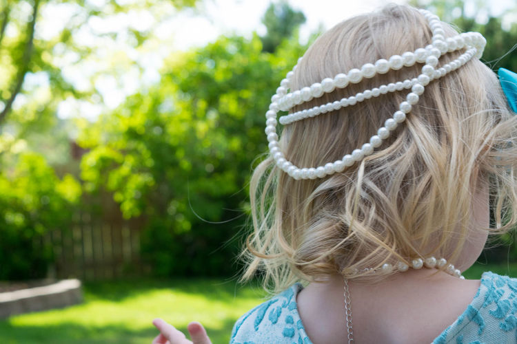 Rear View Of Toddler Wearing Pearl Necklace On Head In Back Yard
