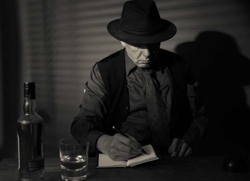Film Noir reloaded: The dirty old detective in his bureau talking to a new client Acting Adult Hat Writing Alcohol Bottle Detective Monochrome Old Person Old Person Sitting One Man Only One Person Portrait Studio Shot Table
