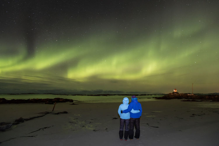 Couple standing on beach under sky illuminated by aurora borealis Adult Astronomy Atmospheric Mood Aurora Borealis Aurora Polaris Beach Beauty In Nature Cold Temperature Dramatic Sky Full Length Green Color Idyllic Illuminated Lighthouse Lofoten And Vesteral Islands Night People Polar Climate Rear View Scenics Sea Sky Space And Astronomy Star - Space Togetherness The Great Outdoors - 2017 EyeEm Awards Lost In The Landscape