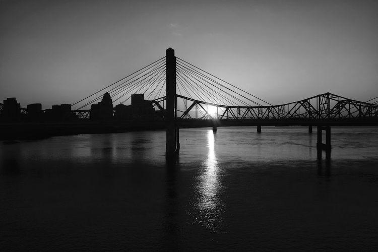 Silhouette of suspension bridge over river