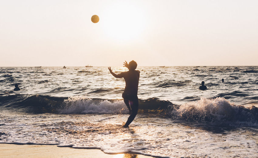 Man playing with ball in sea against sky