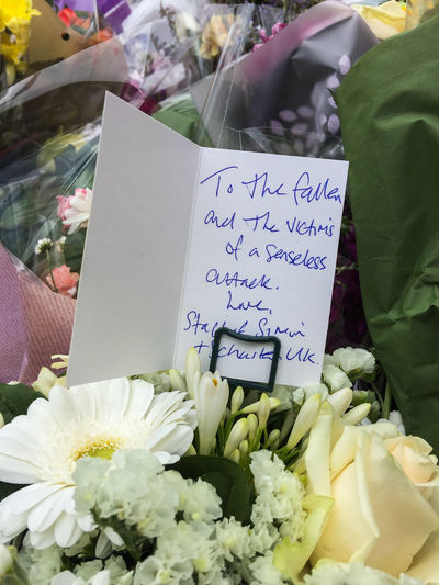 Closeup of memorial flowers and a card left at the site of the London Bridge terror attack. London London Bridge Memorial Bouquet Card Close-up Communication Day Flower Message No People Outdoors Terrorism Text