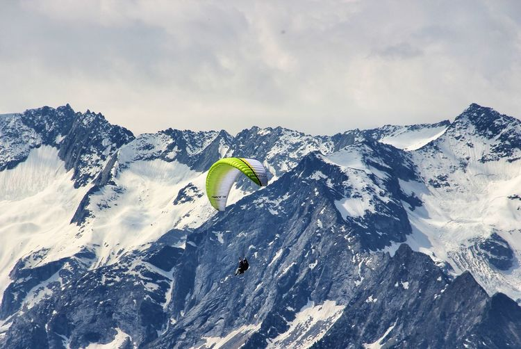 High Angle View Of Person Paragliding Over Snowcapped Mountains