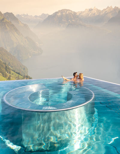 People swimming in pool against sea