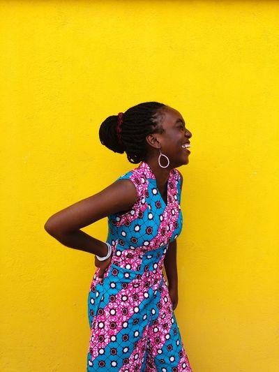 Cheerful woman standing against yellow background