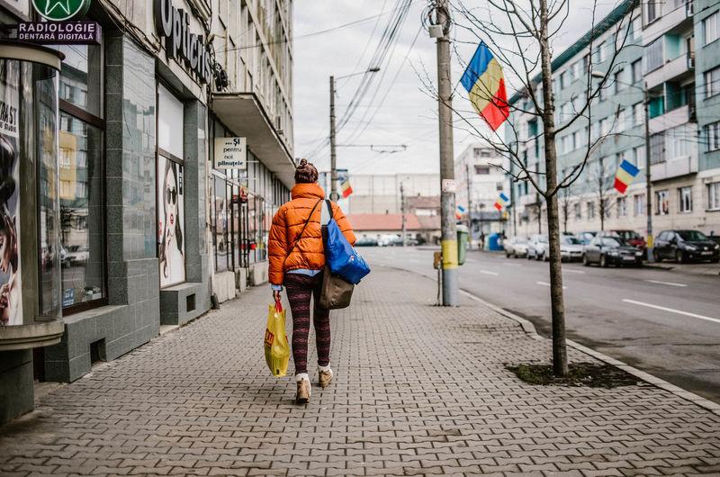 Rear view of man walking on footpath in city
