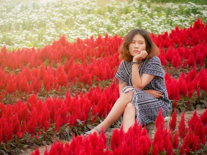 Portrait of woman on red flowering plants
