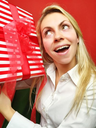 Portrait of smiling young woman with christmas gift