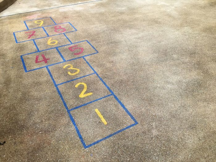 Hopscotch on cement floor. Happy Fun Jump Kids Play High Angle View Chalk Drawing Sunlight Multi Colored Art And Craft Creativity Street Outdoors