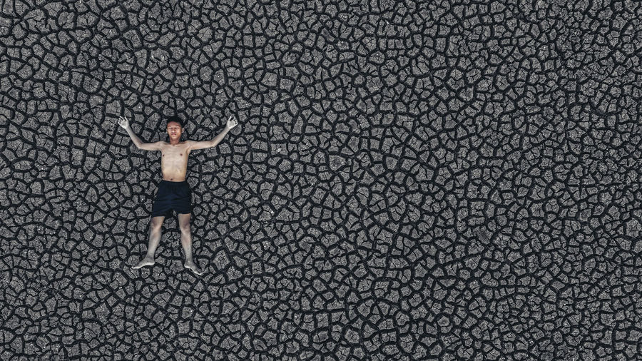 High angle view of shirtless boy with arms outstretched lying on cracked land