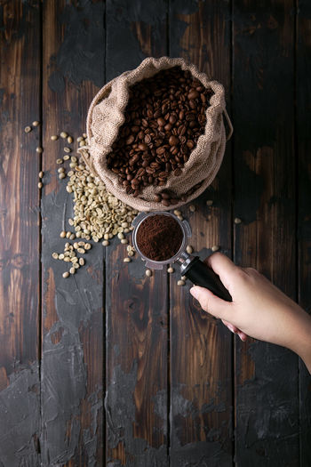 Female hand holding portafilter over textile bag with coffee beans over rustic wooden background. Top view Beans Cezve Dark Moka Rustic Wood Bag Coffee Coffee - Drink Drink Female Food Food And Drink Hand Holding Human Hand Mokapot Portafilter Textile Unrecognizable Person Wood - Material