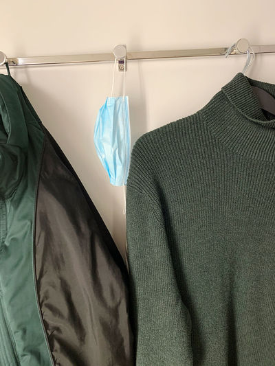 Close-up of clothes hanging on rack against wall