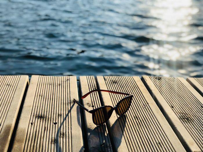 Black sunglasses on wooden pontoon near the water