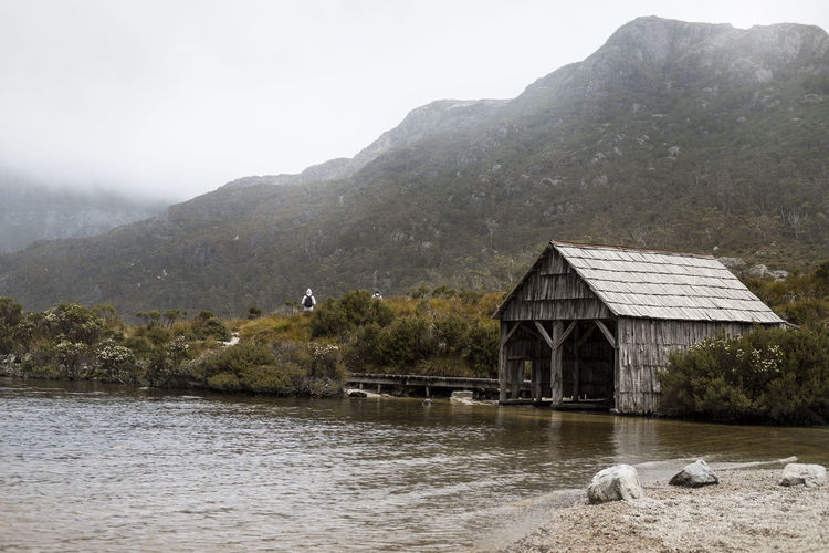 A boat house at Dove Lake in Cradle Mountain National Park Hiking Low Clouds Architecture Beauty In Nature Boat House Building Building Exterior Built Structure Day Fog House Lake Mountain Mountains Nature Outdoors Scenics - Nature Shed Sky Tranquil Scene Tranquility Tree Water Waterfront